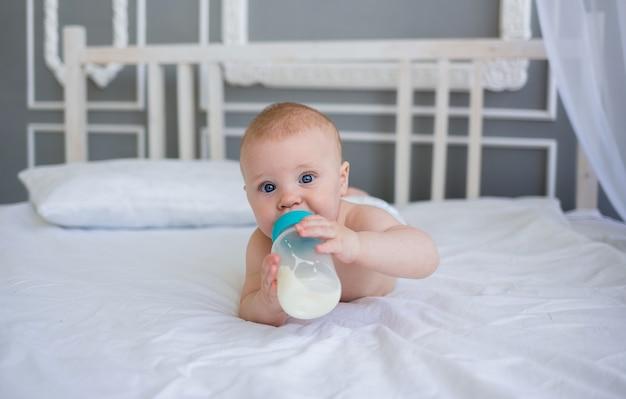 Un bambino piccolo in un pannolino è sdraiato sul letto e beve il latte da una bottiglia