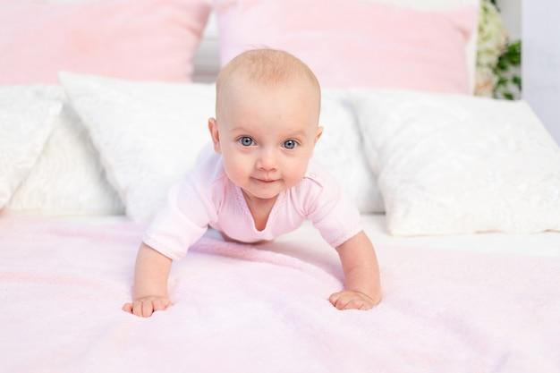 Piccola neonata di 6 mesi che striscia su un letto bianco e rosa a casa, guardando la telecamera, posto per il testo