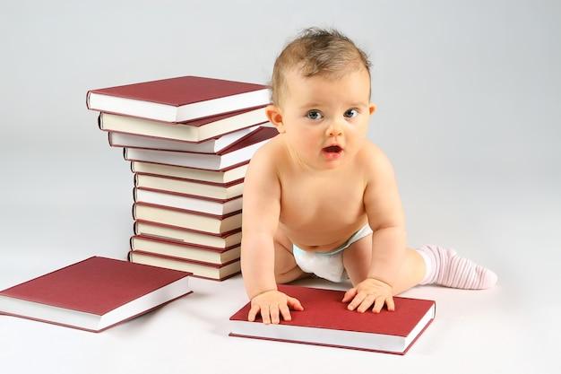 Piccola bambina e tanti libri rossi con copertina rossa