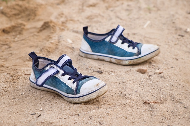 Piccole scarpe per bambini sulla sabbia. scarpe da ginnastica vuote per bambini sulla spiaggia. concetto di vacanza estiva.