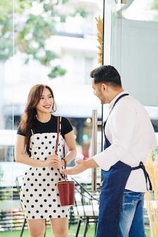 Il proprietario di una piccola pasticceria apre la porta per una donna carina, le fa un gesto di benvenuto e la invita a entrare