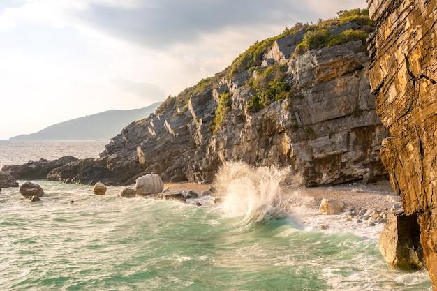 Piccola spiaggia su una spiaggia rocciosa. serata estiva e surf spray