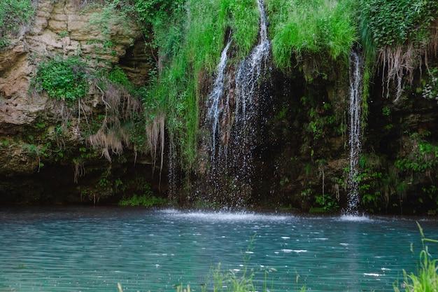 Piccola bella cascata con spazio copia lago blu