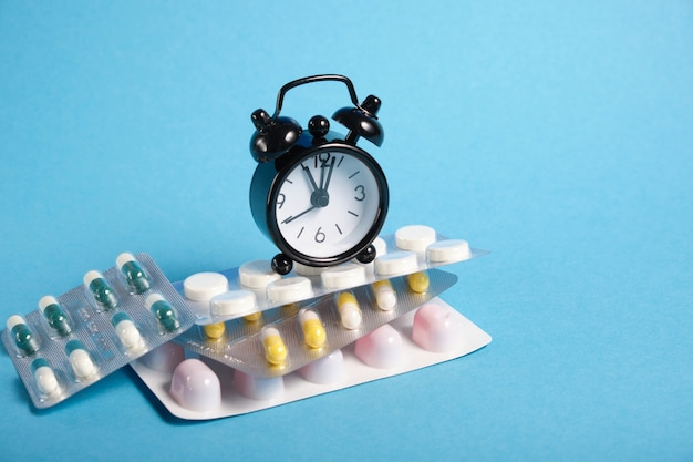 Piccola sveglia nera su una pila di confezioni di pillole, sfondo blu, copia spazio, data di scadenza del concetto di farmaci