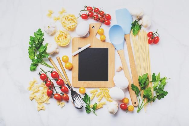 Piccola lavagna con copia spazio circondato da ingredienti per cucinare diversi tipi di pasta, condimenti, utensili, verdure crude sane sparse sullo sfondo di marmo chiaro