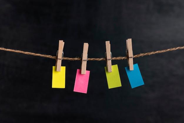 Piccola carta bianca multicolore da appendere con mollette su corda su superficie nera. copia spazio. posto per il tuo testo.