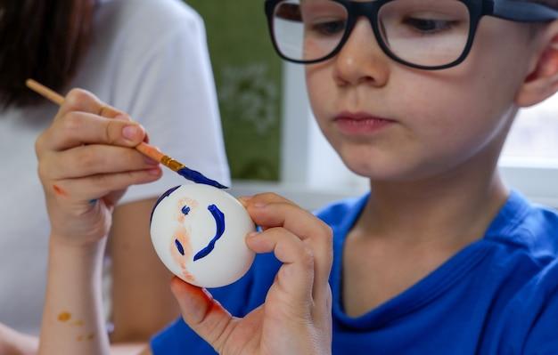 Un piccolo ragazzo biondo dipinge le uova per le vacanze di pasqua nella cucina di casa al chiuso