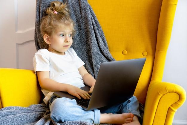 Una piccola ragazza bionda sembra molto sorpresa e guarda il suo laptop mentre è seduta su una sedia a casa