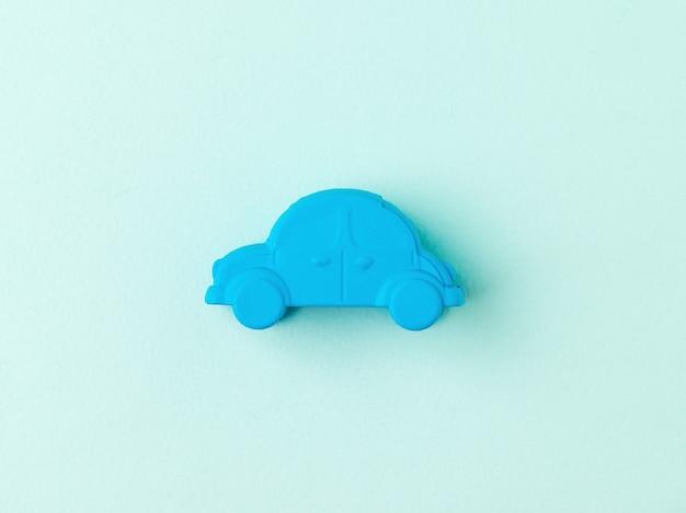 Una piccola macchinina blu su sfondo azzurro. il concetto di un veicolo popolare.