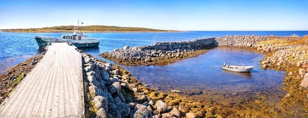 Una piccola barca in una baia di pietra e una grande nave su un molo di legno sulle isole zayatsky. iscrizione: san nicola
