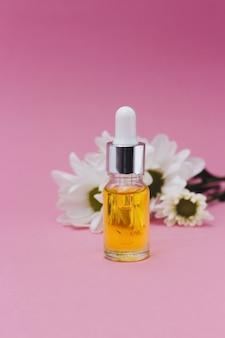 Piccola bottiglia di olio cosmetico per cuticola con pipetta cosmetica per bottiglia di vetro contagocce fiori su superficie rosa