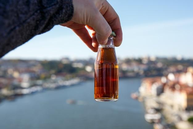 Piccola bottiglia di vino porto all'aperto con il fiume douro e la città di porto