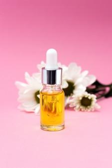 Piccola bottiglia con olio cosmetico massaggio olio per cuticole tintura infusione estratto e fiori di gelsomino da vicino aromaterapia manicure naturale spa fatta in casa e concetto di erboristeria copia spazio