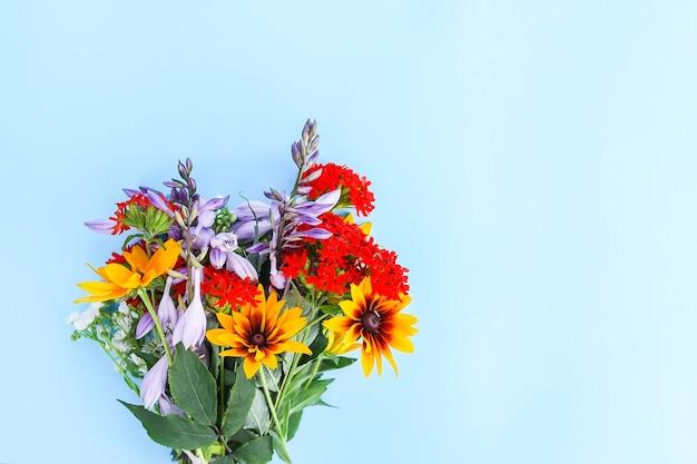 Piccolo bouquet di fiori da giardino su fondo azzurro. campanula decorativa viola, lychnis e rudbeckia o piante di susan dagli occhi neri. modello floreale festivo. progettazione di biglietti di auguri. vista dall'alto.