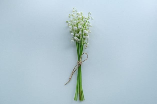 Piccolo bouquet di mughetti con corda artigianale su uno spazio bianco, vista dall'alto, copia spazio, posto per il testo