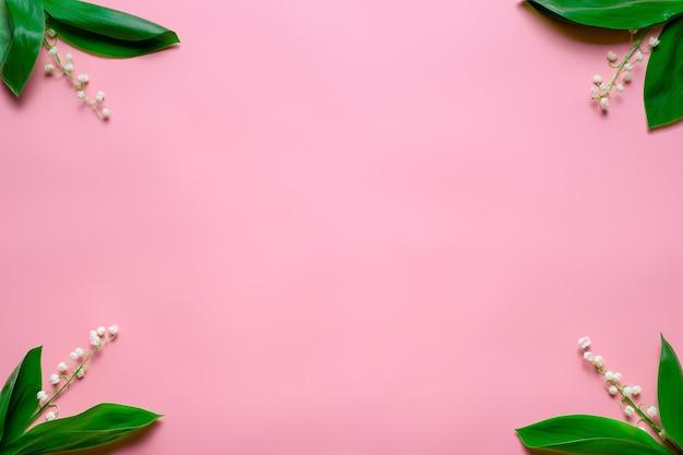 Piccoli mazzi di mughetto negli angoli con copia spazio piatto con sfondo rosa