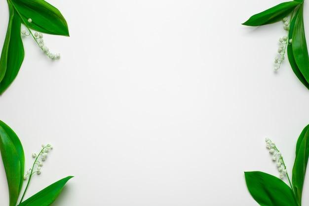 Piccoli mazzi di mughetto negli angoli con spazio vuoto piatto con sfondo bianco