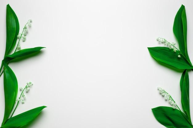 Piccoli mazzi di mughetti ai lati come bordi floreali con spazio per la copia distesi con...