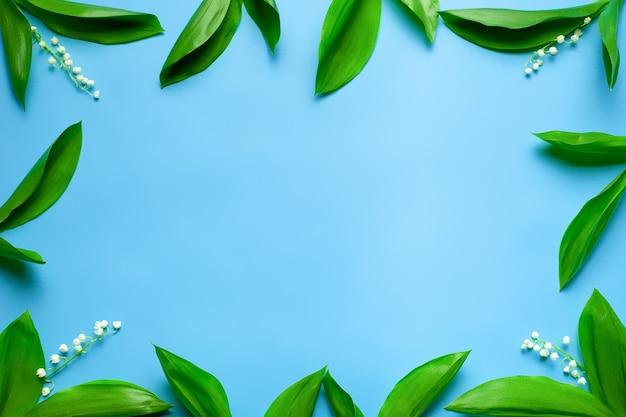 Piccoli mazzi di fiori primaverili come cornice floreale con copia spazio piatto con sfondo blu