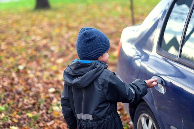 Un ragazzino si avvicina alla macchina e apre la portiera