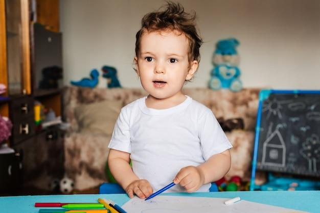 Un bambino disegna su fogli di carta sdraiati sul tavolo con matite colorate
