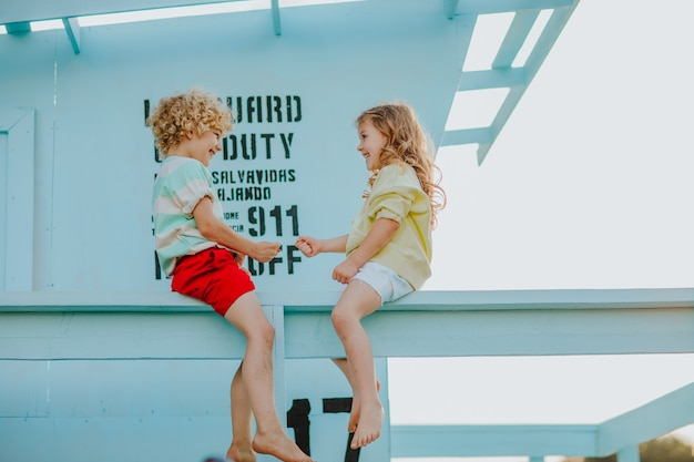 Piccolo ragazzo e ragazza con abiti estivi seduti sulla torre del bagnino in spiaggia