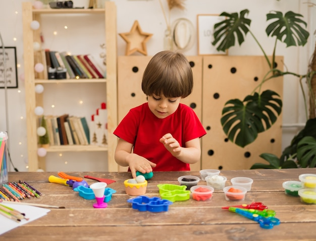 Piccolo ragazzo con una maglietta rossa si siede a un tavolo di legno e scolpisce dalla plastilina