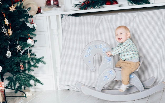 Piccolo ragazzo a cavallo nella stanza bianca che decora per le vacanze di natale e invernali. giocare da soli e divertirsi. parte dell'albero di natale verde nella foto