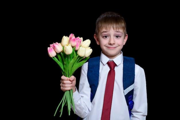 Piccolo ragazzo in una camicia con cravatta e borsa di scuola che tiene un mazzo di tulipani. isolare su sfondo nero.
