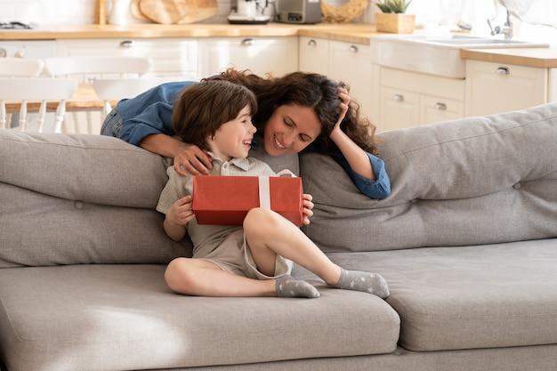 Il piccolo ragazzo di sedersi sul divano tiene la scatola con il regalo di una madre single amorevole festeggia il compleanno a casa