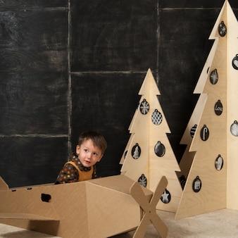 Un ragazzino siede in un aeroplano giocattolo di cartone vicino ad alberi di natale di legno