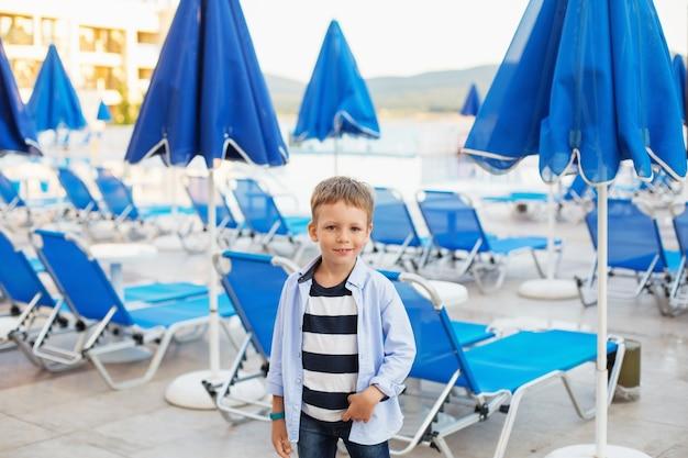 Un bambino si trova tra gli ombrelloni blu e le sdraio nel parco dell'hotel in una località estiva.
