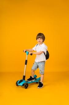 Piccolo ragazzo sta con uno scooter su una superficie gialla con spazio per il testo. sport per bambini