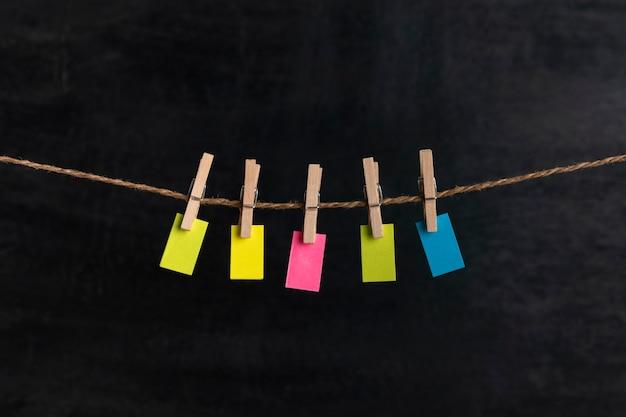 Piccola carta luminosa da appendere con mollette su corda. superficie nera. copia spazio. posto per il tuo testo.