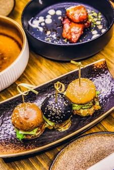 Piccoli hamburger serviti su un piatto come antipasti