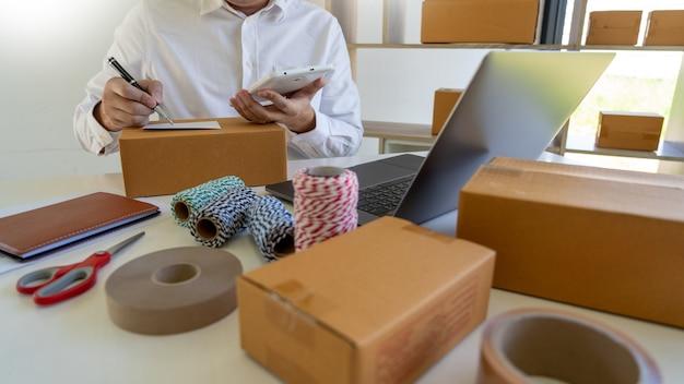 Piccolo imprenditore pmi, giovane uomo asiatico che lavora con computer portatile e scatola di imballaggio di consegna