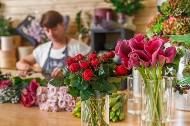Piccola impresa. fiorista maschio sfocato nel negozio di fiori. studio di progettazione floreale, realizzazione di decorazioni e allestimenti. consegna fiori, creazione ordine