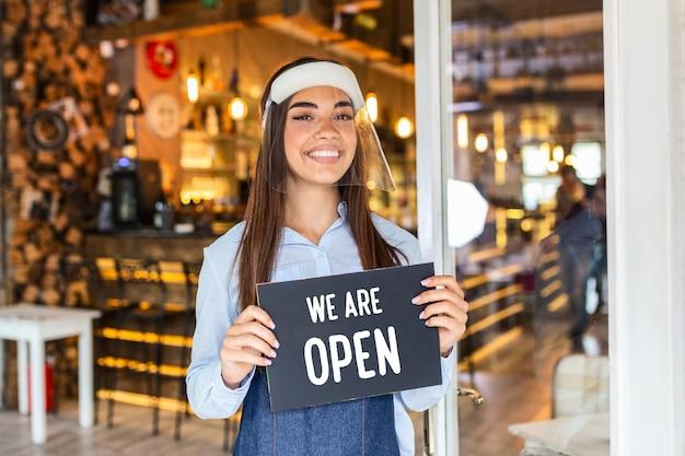 Piccolo imprenditore sorride mentre tiene in mano il cartello per la riapertura del locale dopo la quarantena a causa del covid-19. donna con il segno della holding della visiera siamo aperti, sosteniamo le imprese locali.
