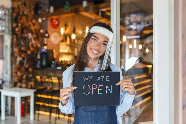 Piccolo imprenditore sorridente mentre tiene in mano il cartello per la riapertura del locale dopo la quarantena a causa del covid-19. donna con il segno della holding della visiera siamo aperti, sosteniamo le imprese locali.