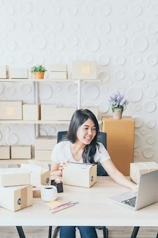 Proprietario di una piccola impresa, donna che controlla l'ordine di acquisto nel computer portatile