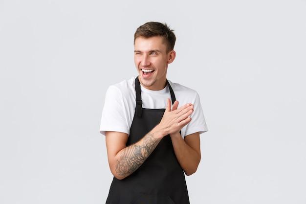 Proprietari di piccole imprese, caffetteria e concetto di personale. barista divertente subdolo e intelligente in grembiule nero, lavoratore del bar che si sfrega le mani come si aspetta piacere o soddisfazione dal piano compiuto, sorridendo sornione