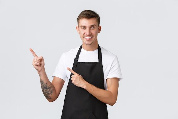 Proprietari di piccole imprese, caffetteria e concetto di personale. barista simpatico e simpatico, ragazzo in grembiule nero che punta le dita a sinistra e sorride, invita a godersi un drink al caffè, sfondo bianco