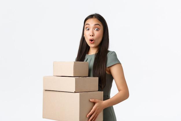 Proprietari di piccole imprese, avvio e lavoro dal concetto di casa. la ragazza asiatica sorpresa e stupita raccoglie i suoi articoli di acquisto nell'ufficio postale. la donna di affari stupita trasporta gli ordini alla società di consegna