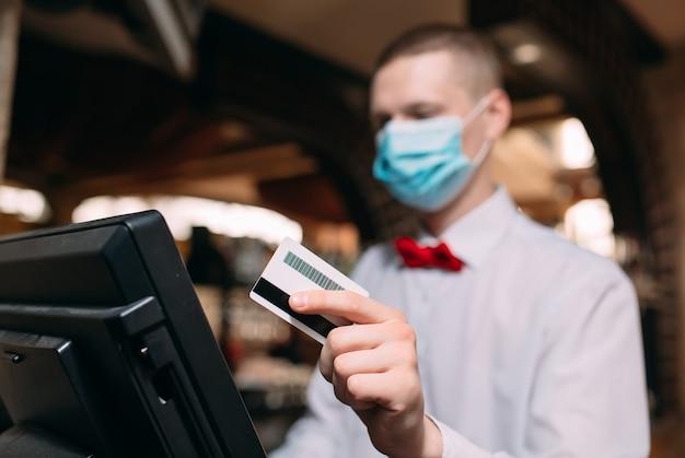 Piccole imprese, persone e concetto di servizio. uomo o cameriere in maschera medica al bancone con cashbox lavorando al bar o alla caffetteria.