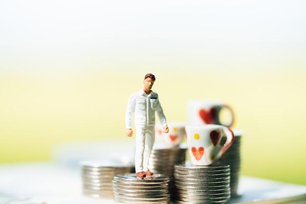 Piccoli uomini d'affari in piedi sulla pila di monete con sfondi della città.