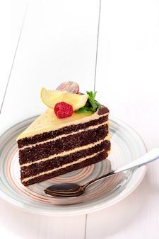 Piccola torta con ripieno diverso su un piatto bianco. tavolo in legno bianco. natura morta. copia spazio