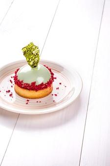 Piccola torta con ripieno diverso su un piatto bianco tavolo in legno bianco