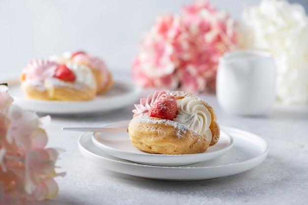 Piccole torte con panna montata e fragole, immagine di messa a fuoco selettiva