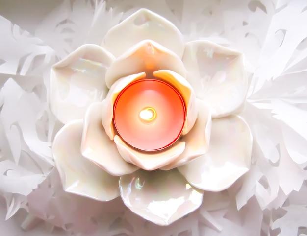 Piccola candela in elegante candeliere su sfondo ornamentale di carta bianca