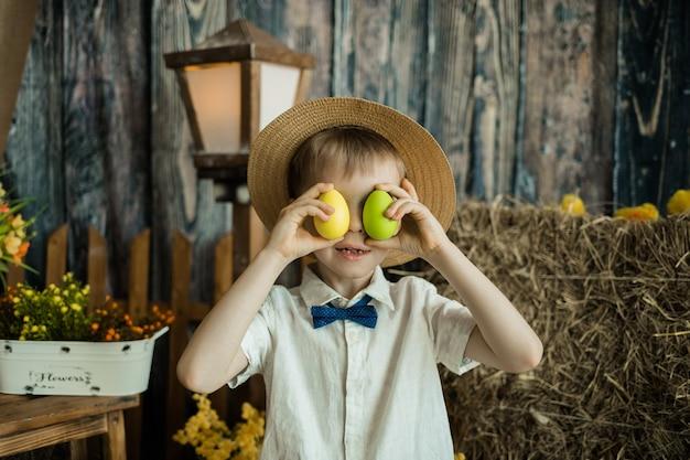 Piccolo ragazzo caucasico con una maglietta e un cappello di paglia si copriva gli occhi con uova colorate. pasqua per i bambini